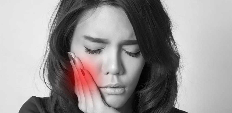 black and white a woman holds her cheek which is in red signifying that she is in pain