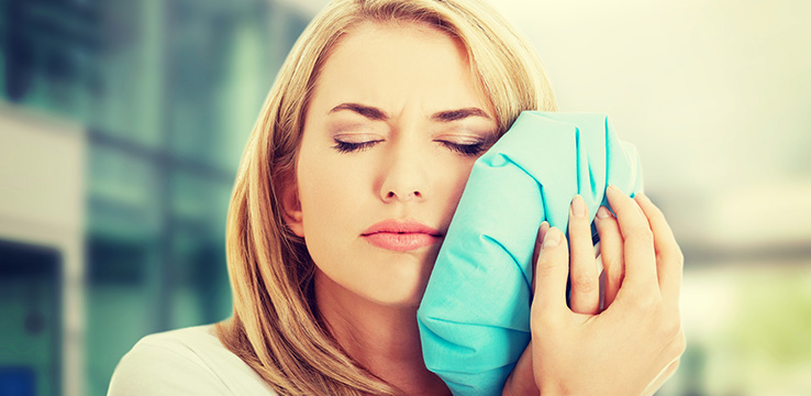 woman holding an icepack to her face with her eyes closed