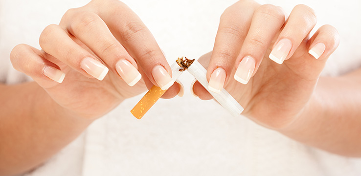 the hands of a woman breaking a cigarette in half