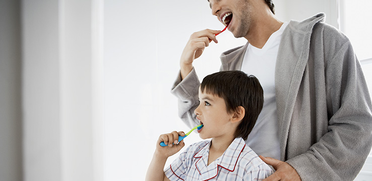 father and son brushing their teeth together