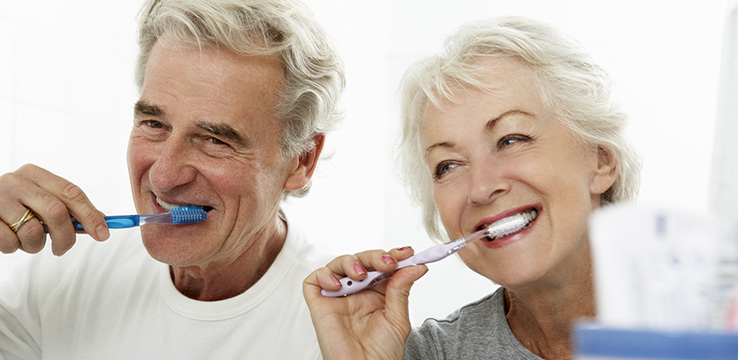 elderly couple brushing their teeth together they look happy