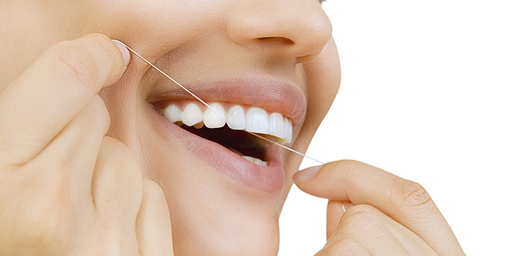 close up of woman's mouth as she uses dental floss on her top teeth.