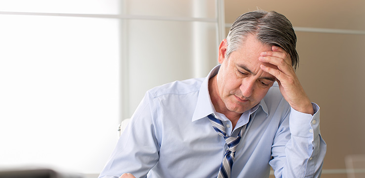 older man looking disheveled holding his head and looking down