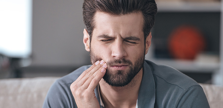 man with big hair and a hipster beard pushing on his cheek with his eyes closed as if he is in pain
