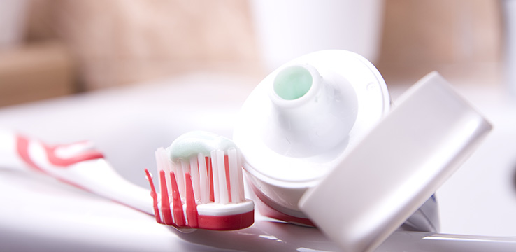 tube of tooth paste with the lid off and a toothbrush with toothpaste on it